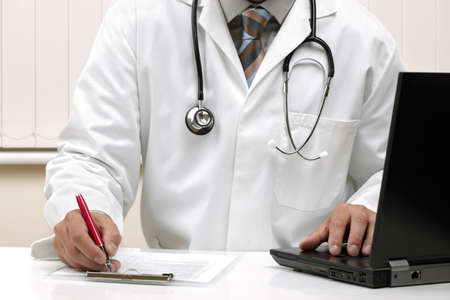 unrecognisable people: Doctor writing patient notes on a medical examination form or prescription