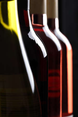 Red, white and rose wine bottles in a row photo