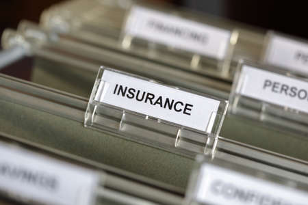 insurance themes: Inside of a filing cabinet with green folders and focus on insurance label Stock Photo