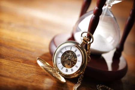 reloj antiguo: Hora de vidrio o de reloj de arena con el reloj de bolsillo de la vendimia, símbolos de tiempo, con copia espacio
