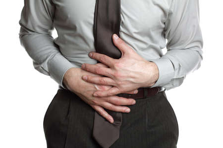 food poisoning: Businessman holding his stomach in pain or indigestion Stock Photo