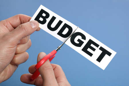 cutting costs: Scissors cutting the word budget concept for recession or credit crisis Stock Photo