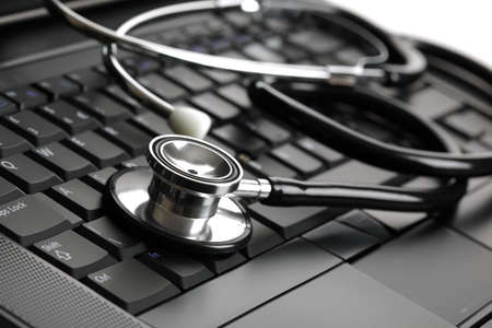 computer key: Stethoscope resting on a computer keyboard - concept for online medicine or IT support