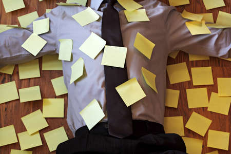 overloaded: Over worked and stressed businessman lying on his back covered in yellow notes Stock Photo