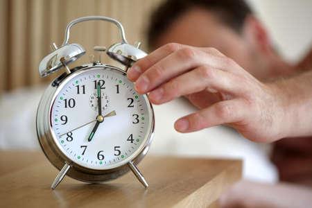 7 で朝の目覚まし時計をオフにベッドで横になっている男