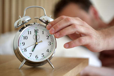 Man lying in bed turning off an alarm clock in the morning at 7am Stock Photo