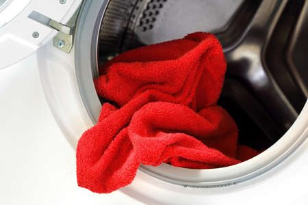 launderette: Door open on washing machine with red towel inside
