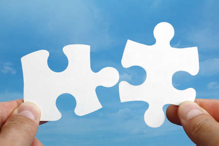 two pieces: Holding two jigsaw pieces of a blank puzzle trying to fit together against blue sky background