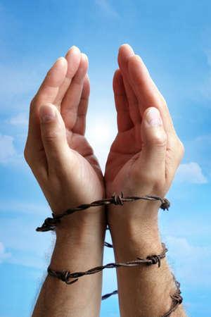 derechos humanos: Manos levantadas a una luz brillante en el cielo atadas con alambre de púas