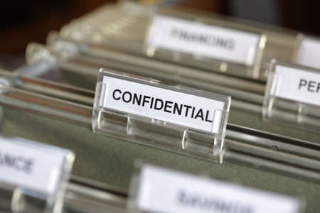office cabinet: Inside of a filing cabinet with green folders and focus on confidential label