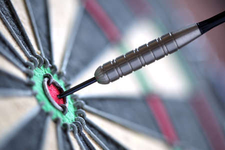 expertise concept: Dart in bulls eye of dartboard with shallow depth of field concept for hitting target