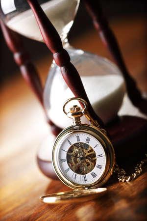 arena: Hora de vidrio o de reloj de arena con el reloj de bolsillo de la vendimia, símbolos de tiempo