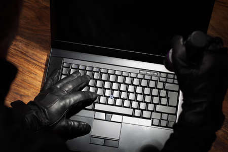 Burglar holding a torch stealing data from a laptop concept for computer security, corporate or identity theft photo
