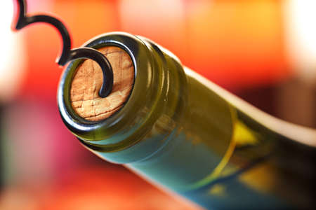Opening a wine bottle with a cork screw in a restaurant Archivio Fotografico