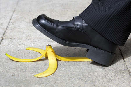 tripping: Businessman about to slip and fall on a banana skin