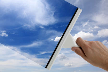 cleaning window: Using a squeegee to clear the blue sky above