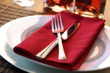 luxury restaurant: Elegant table setting with fork, knife and red napkin Stock Photo