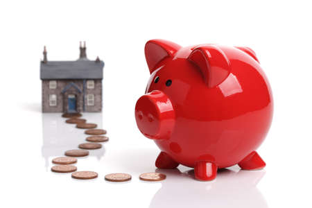 bank: Real estate or home savings - red piggy bank, coins and a house Stock Photo