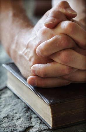 biblia: Las manos juntas en oraci�n durante una Santa Biblia que descansa sobre una pila bautismal de piedra