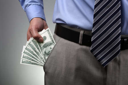 Businessman with money in suit trouser pocket Stock Photo