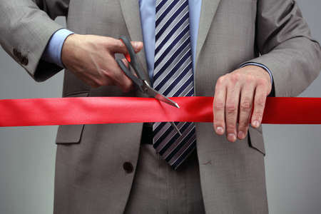 stores: Het snijden van een rood lint met een schaar concept voor de nieuwe onderneming of openingsceremonie