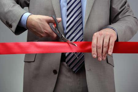 taglio del nastro: Taglio un nastro rosso con le forbici concetto per la nuova impresa o cerimonia di apertura