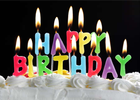 velitas de cumpleaños: Feliz cumpleaños velas coloridas ardiendo en una torta Foto de archivo