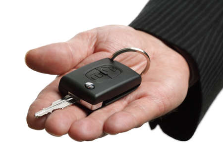Car salesman or rental man giving a car key to someone Stock Photo - 25717850
