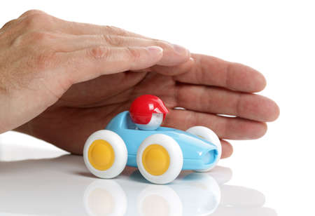 car loan: Toy car protected by human hands on white background
