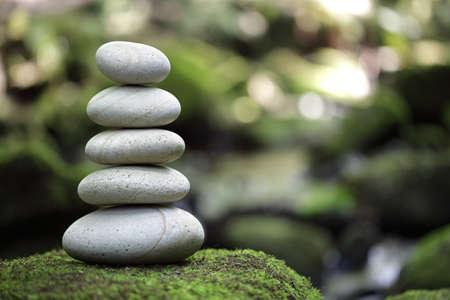 piedras zen: Pila de piedras de cantos rodados junto a un arroyo en un bosque