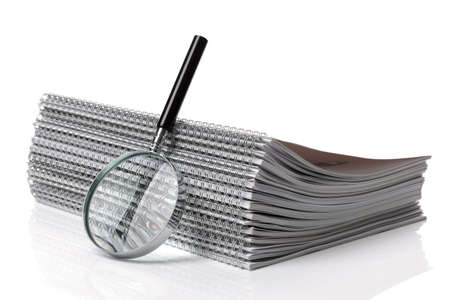Magnifying glass with stack of spiral notebook documents photo