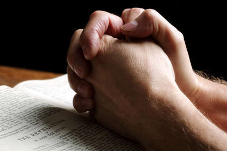Mans hands folded in prayer over an open Holy Bible Stock Photo