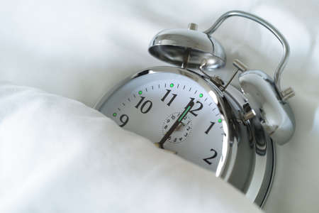 overslept: Alarm clock in bed concept for overslept or bed time