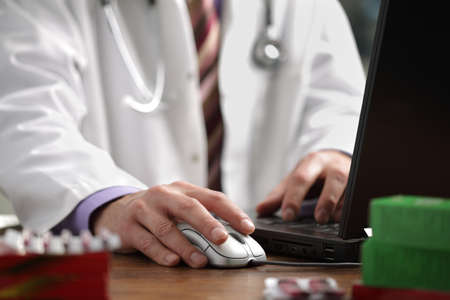 Doctor using a laptop computer to prepare an online prescription photo