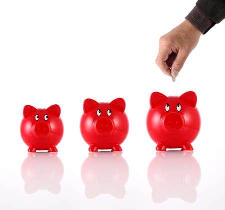 miserly: Hand putting coin into three hopeful piggy banks Stock Photo