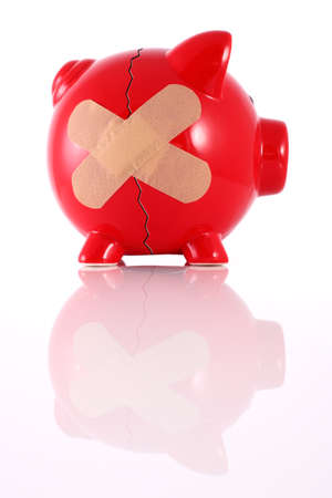 Cracked piggy bank with plaster representing financial problems Stock Photo