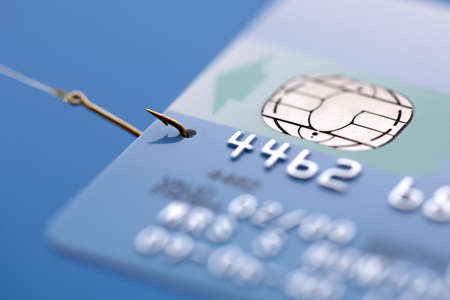 phishing: Credit card caught on a fishing hook concept for addiction to spending with credit or phishing Stock Photo