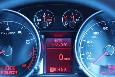 Speedometer, revcounter, fuel and temperature gauge of a sports car dashboard