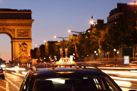 Parisian taxi, with the Arc de Triumph and traffic light trails in the background photo