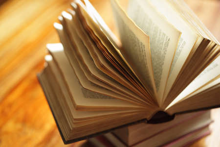 bible reading: Book or bible on top of a stack of books on a wooden desk in library or classroom