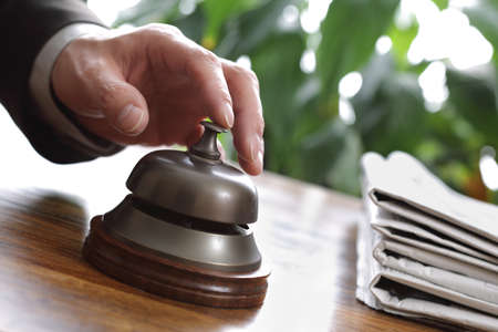 Businessman ringing a hotel reception service bell to attract attention photo
