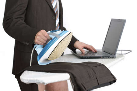 Businessman working from home on laptop computer whilst doing the chores photo