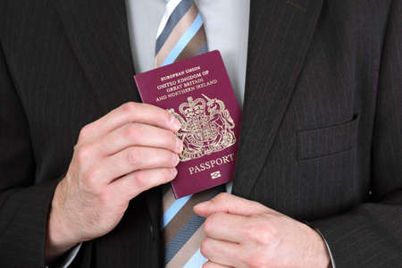 Businessman presenting a British passport at customs or check in area