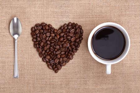tomando refresco: Coraz�n forma de granos de caf� con una cuchara y una taza de caf� en la arpillera ortograf�a me encanta el caf� Foto de archivo