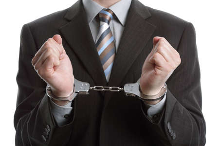 Corporate crime concept, businessman wearing handcuffs photo
