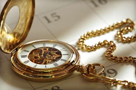 reloj antiguo: Primer plano de un reloj de bolsillo de oro en un calendario en la luz del sol Foto de archivo