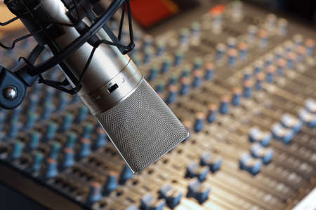 Studio microphone in front of mixing console in recording studio photo