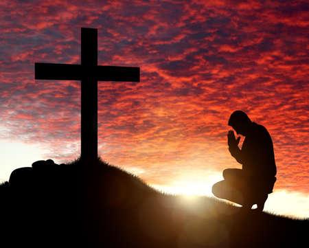 ひざまずく: 宗教、信仰、愛と霊性の天 cloudscape 日没概念と十字架への祈りの男のシルエット