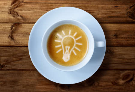 inspirations: Coffee cup with light bulb idea in the froth concept for ideas, creativity and innovation Stock Photo