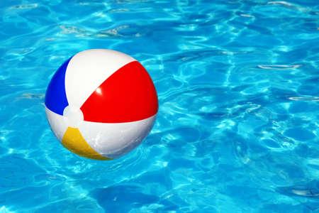 natacion: Pelota de playa flotando en la piscina concepto abstracto para las vacaciones de verano, la relajación y la diversión bajo el sol